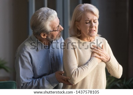 Worried elder senior husband helping supporting mature middle aged wife touching chest having heart attack feeling sudden pain heartburn heartache hurt at home, old couple health problems concept #1437578105
