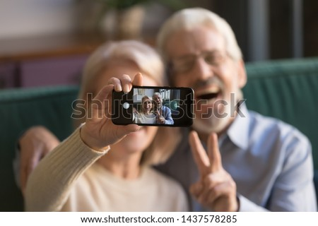Happy old couple taking selfie on cellphone, smiling senior mature spouses middle aged wife and retired husband laughing holding phone make self portrait on smartphone camera, focus on mobile display