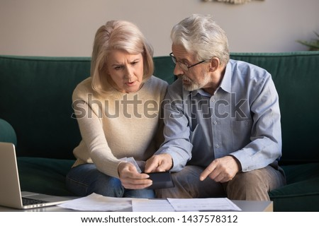 Serious stressed senior old couple worried about paperwork discuss unpaid bank debt calculate bills, shocked poor retired family looking at calculator counting loan payment upset about money problem #1437578312