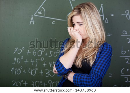 Female student deep thoughts standing at blackboard #143758963