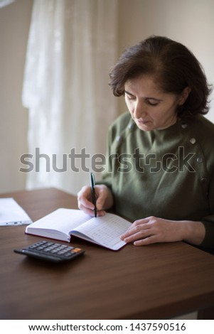 Senior businesswoman working with documents and smartphone at the bright modern Office interior. Elderly woman plans her budget, with a notebook, bills and a credit card.  #1437590516
