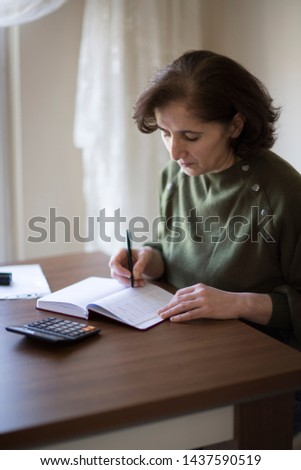 Senior businesswoman working with documents and smartphone at the bright modern Office interior. Elderly woman plans her budget, with a notebook, bills and a credit card.  #1437590519
