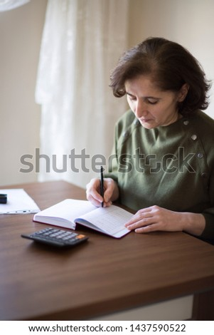 Senior businesswoman working with documents and smartphone at the bright modern Office interior. Elderly woman plans her budget, with a notebook, bills and a credit card.  #1437590522
