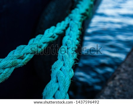 Bright green thick ropes tied tightly for a  secure harbor docking. The boat is docked in the Swedish capital Stockholm. #1437596492