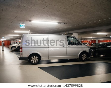 Haarlem, Netherlands - Aug 19, 2018: Dutch underground parking with woman silhouette in background and new Volkswagen transporter silver wan #1437599828