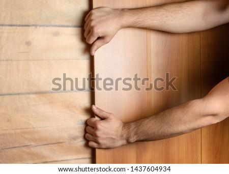 Male hands install MDF panels on the prepared wall #1437604934