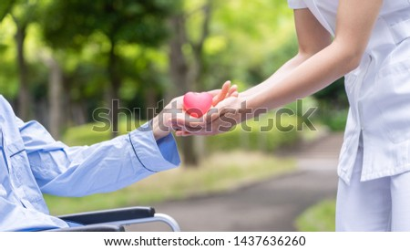 nurse handing over hearts icon to old patient in wheelchair at park #1437636260