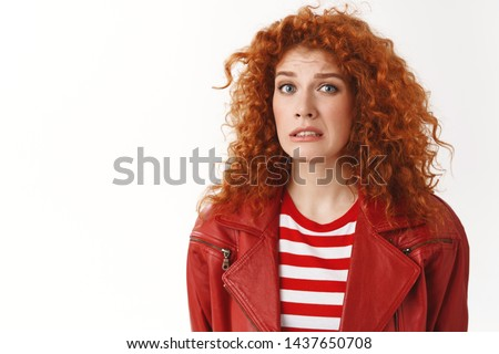 Girl cringing feeling awkward hearing strange weird confession smirking frowning look displeased uncomfortable situation standing distressed doubtful white background hesitating #1437650708