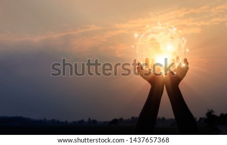 Abstract networking. Technology and communication. Hands holding global network and data exchanges on sunset background.