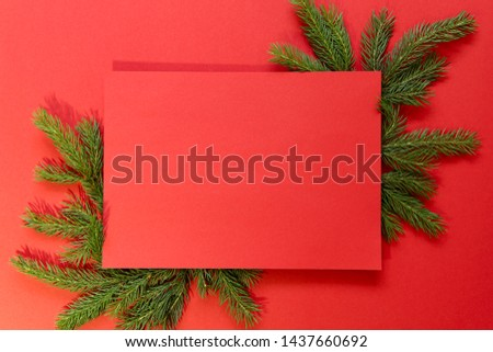 Mockup.Christmas theme. Red background with green branches of spruce. Background, card, empty space in the center, horizontal. Christmas and New Year concept.