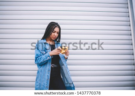 Concentrated female photographer holding vintage camera in hands and editing photos on publicity area, serious african amateur recalls pleasant moments from pictures on old fashioned equipment