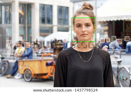 young woman picked out by face detection or facial recognition software - several other faces detected in crowd of people in background #1437798524