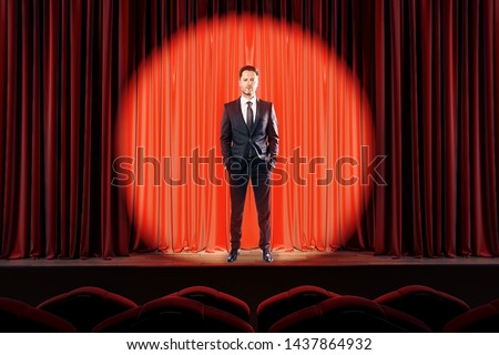 Attractive businessman standing on red stage in spotlighting. Star, show, speech and presentation concept. #1437864932