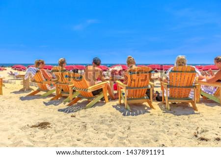 San Diego, California, United States - August 1, 2018: people sunbathe on sea chairs in Coronado Beach along Ocean Boulevard on Pacific Ocean, Coronado Island. Summer season in West Coast. Blue sky. #1437891191