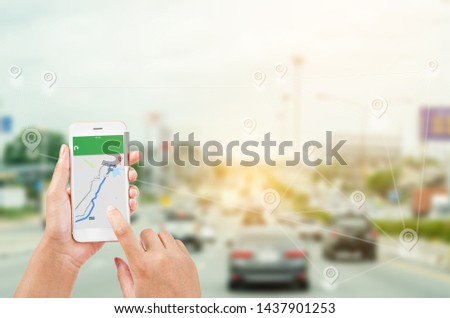 female hands holding a smart phone showing part of navigator map over screen on connection line over the road, Navigation concept. #1437901253
