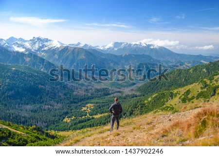 Hiker on the mountain crest enjoying the view. A man tourist on the ridge, seeing the panorama. Central Europe. #1437902246