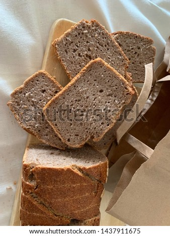 "Traditional Turkish bread is ""Greçka"" over white cover. Scenery contain chopping board, brown paper bag. Greçka make by sour yeast.  #1437911675"