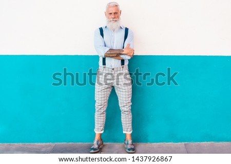Senior hipster man posing with trendy wall background - Trendy male with tattoos wearing fashion clothes - Trend, influencer, and joyful elderly lifestyle concept - Focus on his face #1437926867