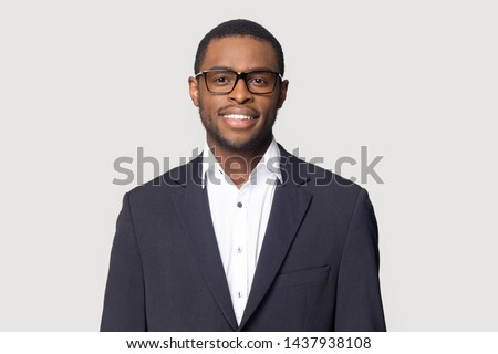 Smiling african American millennial businessman in glasses isolated on grey studio background posing, satisfied successful black male in formal suit wearing spectacles look at camera laughing #1437938108