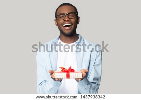 Happy african american male wearing glasses isolated on grey studio background hold wrapped birthday present with red bow, smiling black man in spectacles greeting congratulating give gift box