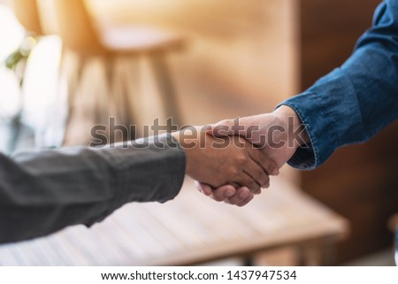 Closeup image of two people shaking hands  #1437947534