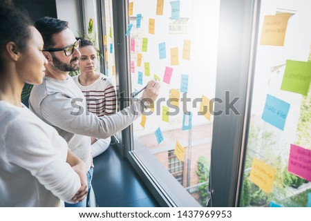 Business people meeting at office and use post it notes to share idea. Brainstorming concept. Sticky note on glass wall. #1437969953