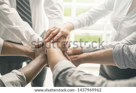 Close up view of young business people putting their hands together. Stack of hands. Unity and teamwork concept. #1437969962