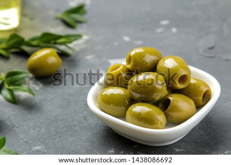 Green olives in a white ceramic bowl with leaves on a dark graphite background. close-up #1438086692