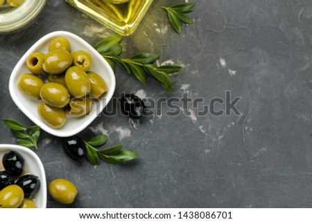 Green and black olives in a white ceramic bowl with leaves on a dark graphite background. top view. space for text #1438086701