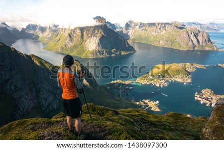 Nature photographer stay at tripod on summit and thinking. Man photographer during hike. Breathtaking view on mountains and village of Reine in Lofoten islands, Norway, from Reinebringen ridge