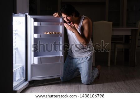 Man breaking diet at night near fridge #1438106798