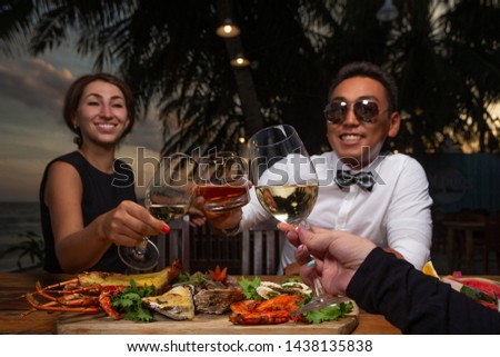 Friends in a seafood restaurant - cheers clink glasses  #1438135838