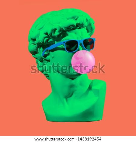 Statue. Isolated. Gypsum statue of David's head. Man. Creative. Plaster statue of David's head in blue sunglasses. Minimal concept art. #1438192454