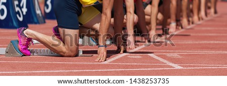 Group of male track athletes on starting blocks.Hands on the starting line.Athletes at the sprint start line in track and field Royalty-Free Stock Photo #1438253735