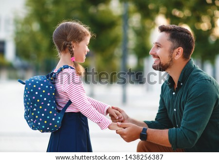 first day at school. father leads a little child school girl in first grade #1438256387