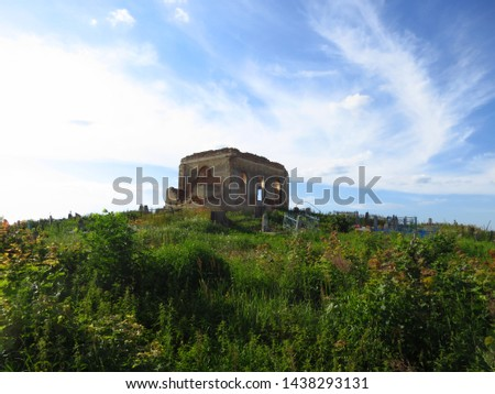 An old cemetery with a ruined drop of red brick against a blue sky #1438293131