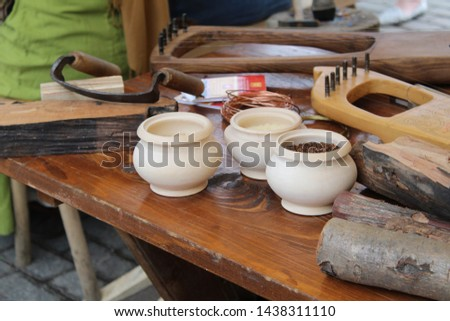 photo workshop.they make ancient musical instruments.stringed instruments.similar to the harp.on a wooden table there are pots.lies a metal wire.firewood.wood for work in the workshop. #1438311110