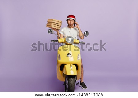 Food delivery concept. Shocked courier takes order over phone from customer, holds stack of cardboad pizza boxes, stops to have break drives fast motorbike, astonished to loose way, doesnt know route #1438317068