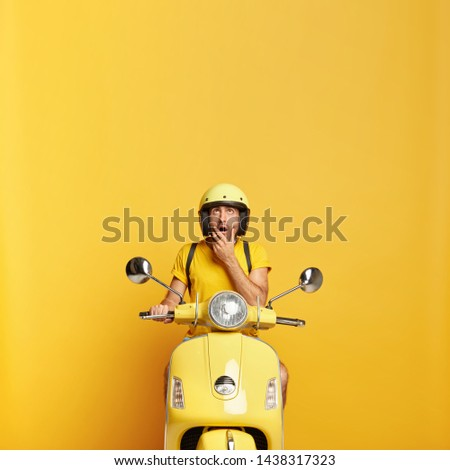 Motocycle taxi driver waits for passenger, wears yellow helmet and t shirt, focused up with thoughtful surprised expression, enjoys travel on scooter maintains safety regulations. Active way of life #1438317323