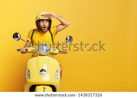 Stupefied male motorbike driver in ptotective helmet, keeps hand near forehead, focused with astonishment into distance, gazes something shocking, isolated on yellow wall. People and riding. #1438317326