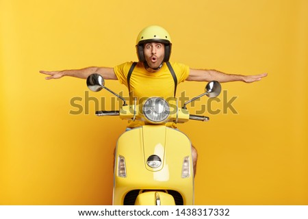 Shocked male motorcyclist travels on motorbike, has adventure trip and feels extreme, keeps hands away from handlebars, spreads sideways, likes active rest during summer, drives on high speed. #1438317332