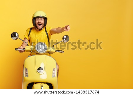 Overjoyed happy male drives motocycle, dressed in casual yellow t shirt and headgear, points happily into distance, notices something awesome, reaches destination on fast transport, enjoys speed #1438317674