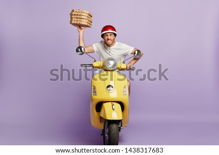 Food service, fast delivery concept. Impatient pizza delivery driver poses on fast motorbike, being in hurry with boxes of fast food, clenches teeth, annoyed with heavy traffic drives to customer home #1438317683