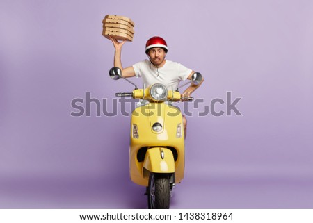 Nervous male courier distributes pizza in cardboard containers on motorbike, tries to reach destination quickly and be punctual, being professional well skilled driver, stuck in traffic jam on his way #1438318964