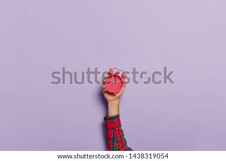Time management, punctuality, awakening concept. Unrecognizable man holds little red alarm clock in hand, shows how much time left, isolated on purple wall. Timekeeper with mechanical watch.