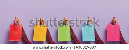 Image of mans hands with various colorful shopping bags isolated on purple background. Black Friday. Consumerism, sale, shopping and purchasing concept. Unknown male customer with many packages #1438319087