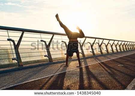 Young man doing exercise early in the morning on a pathway #1438345040