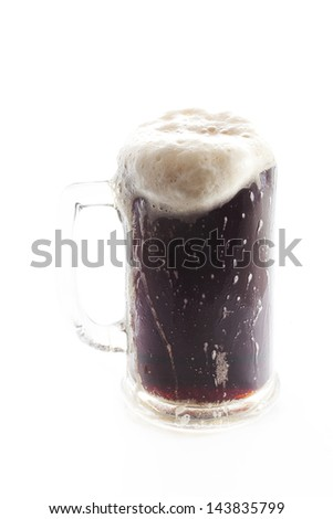 A full pint of beer with froth overflowing from the glass. #143835799