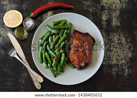 Green pea pods with chili pepper and soy sauce. Meat steak. An example of a balanced diet. Keto diet. Pegan Diet. #1438405652