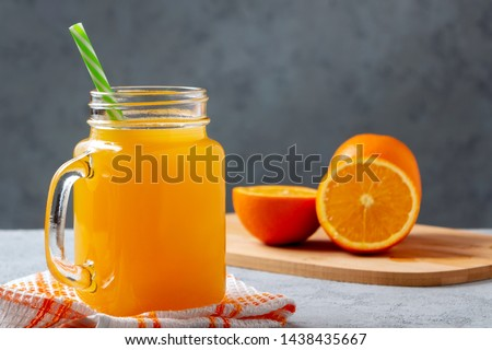 Freshly made citrus juice from oranges in a jar-mug with a straw on gray table